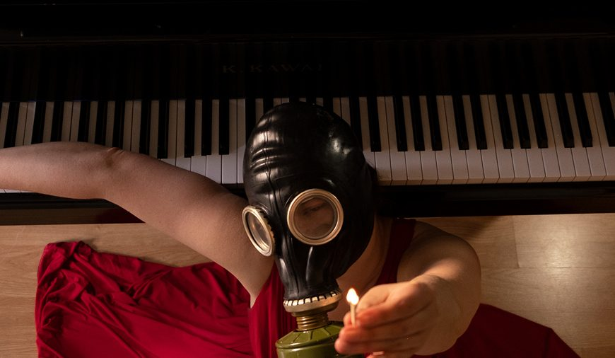 Women with gas mask and piano burning